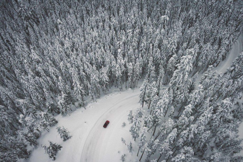Auto tiellä talvisessa metsämaisemassa.