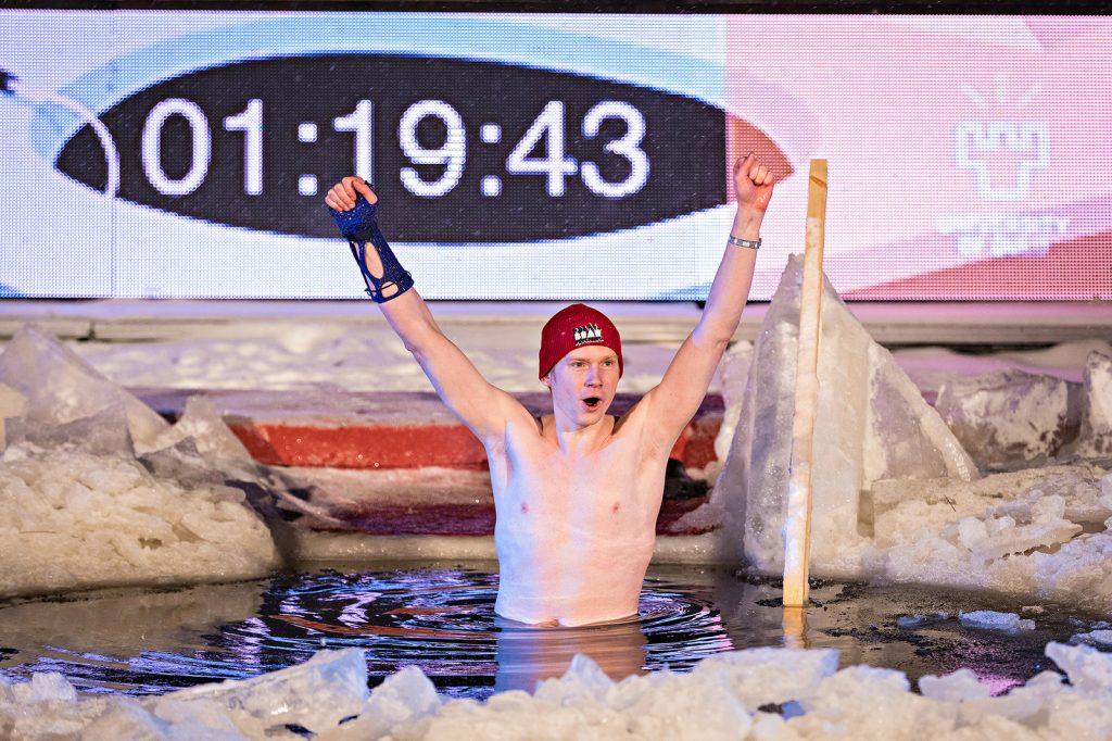 """Pipopäinen tuulettava henkilö on vyötäröään myöten vedessä, jonka ympärillä on jäälohkareita. Taustalla olevalla näytöllä näkyy lukema """"01:19:43""""."""