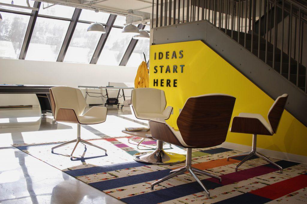 """Avoin työtila, jossa on tuoleja ja pöytiä. Työtilassa on keltainen seinä, jossa lukee teksti """"Ideas start here""""."""