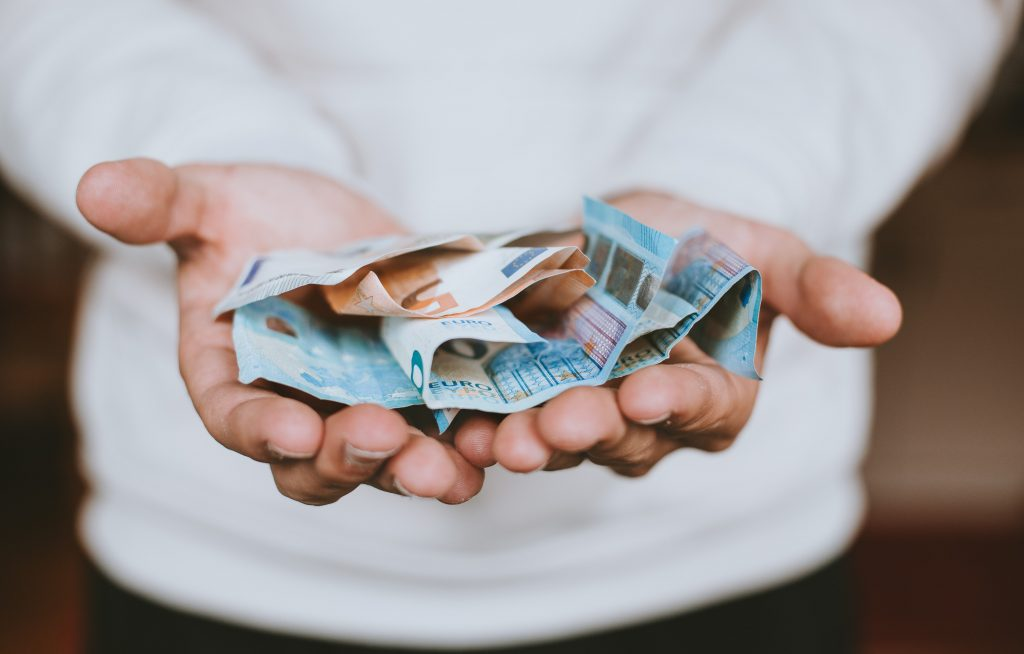 Henkilöllä on kämmenillään euroseteleitä.