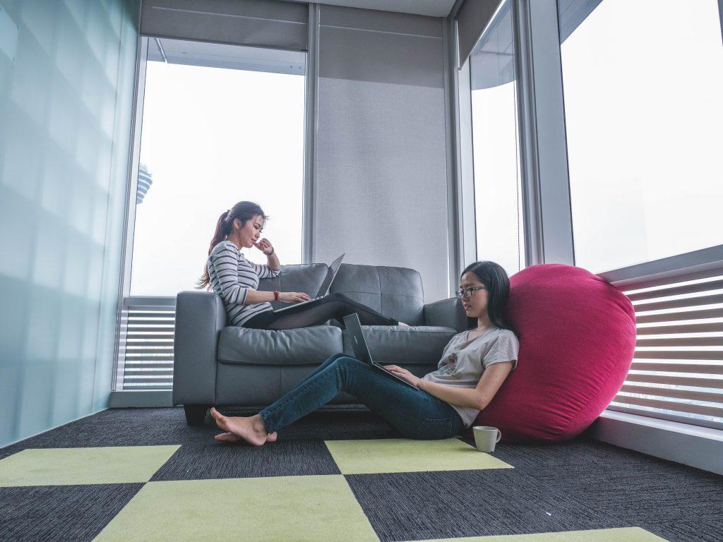 Kaksi henkilöä läppäreiden äärellä. Toinen istuu sohvalla ja toinen lattialla nojaten isoon tyynyyn.