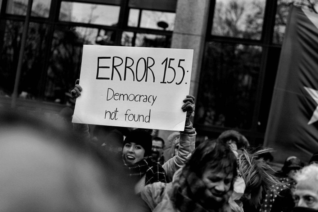 """Mielenosoittaja pitää käsissään kylttiä, jossa lukee """"Error 155: Democracy not found""""."""