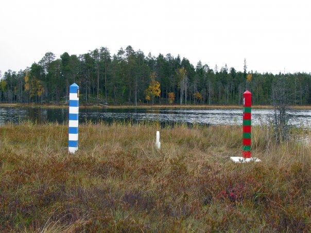 Sinivalkoinen ja punavihreä rajapyykki Suomen ja Venäjän rajalla.