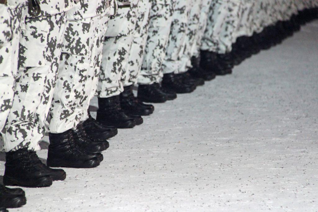 Maastopukuun pukeutuneita henkilöitä rivissä.