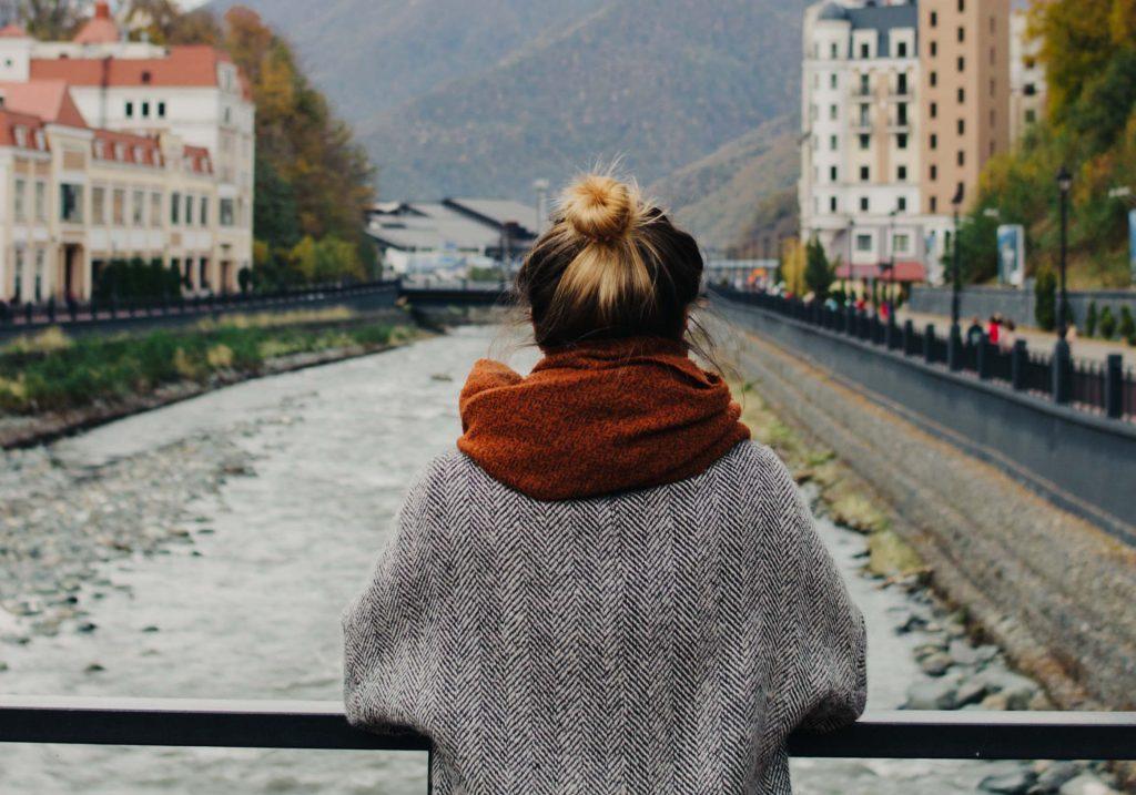 Henkilö nojaa joen ylittävän sillan kaiteeseen.