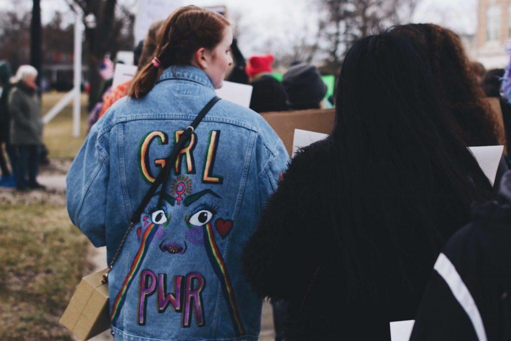 """Henkilöitä ulkona. Etualalla olevalla henkilöllä on farkkutakki, jossa lukee """"Grl Pwr""""."""