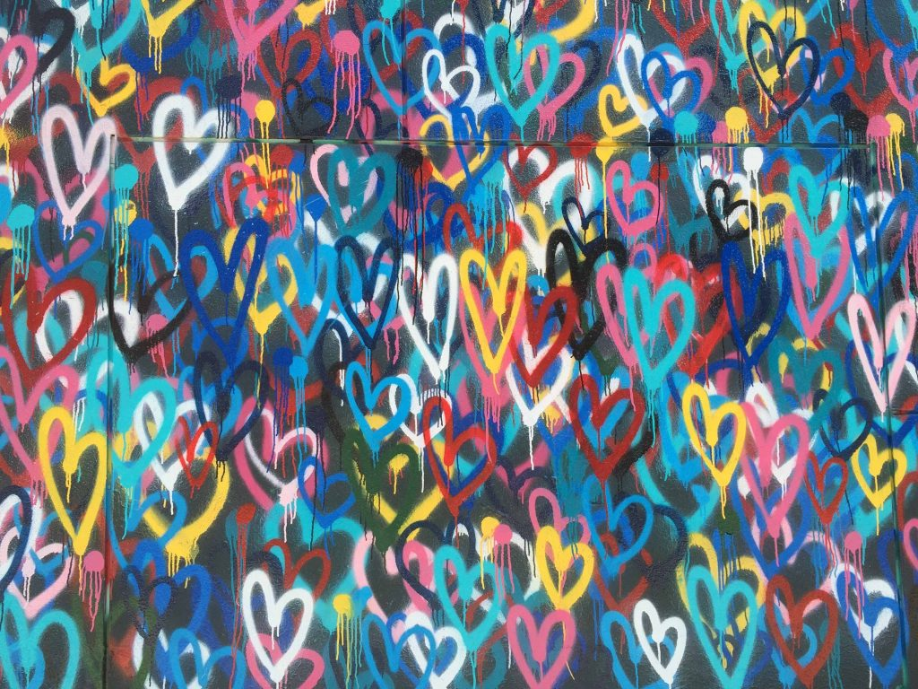Seinä, johon on maalattu spray-maalilla lukemattomia erivärisiä sydämiä.