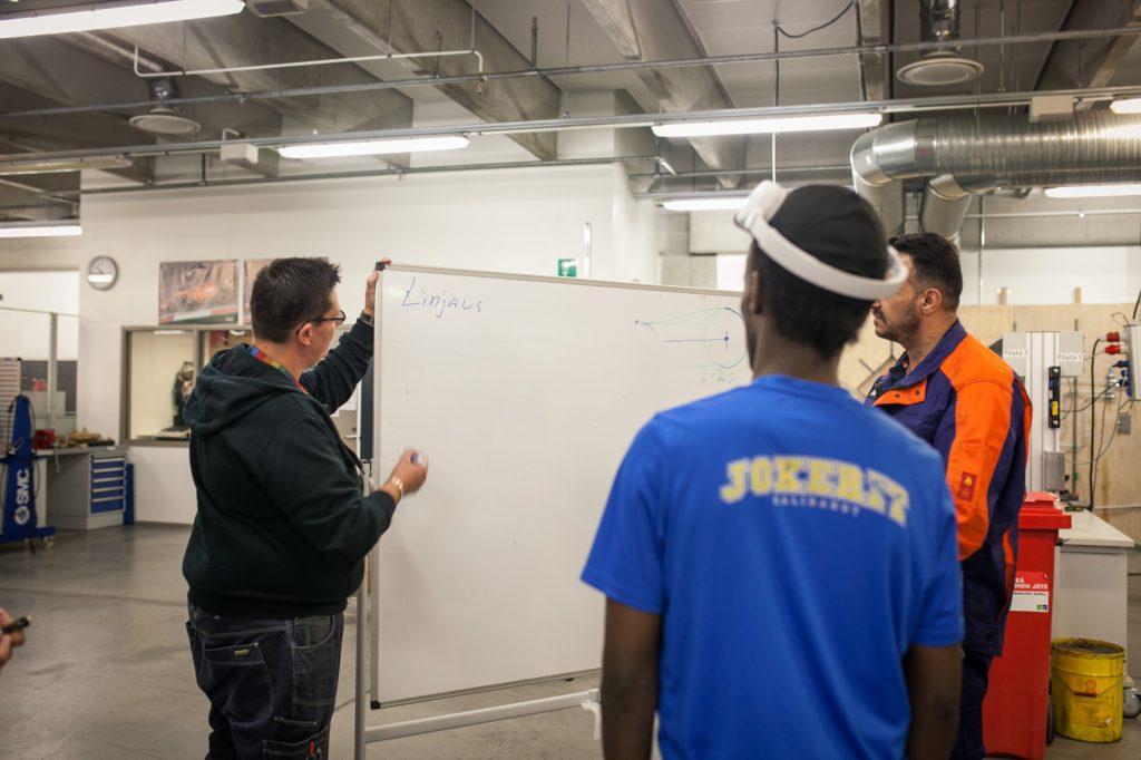 """Kaksi henkilöä katsomassa taululle, jolle kolmas henkilö on kirjoittanut """"Linjaus""""."""