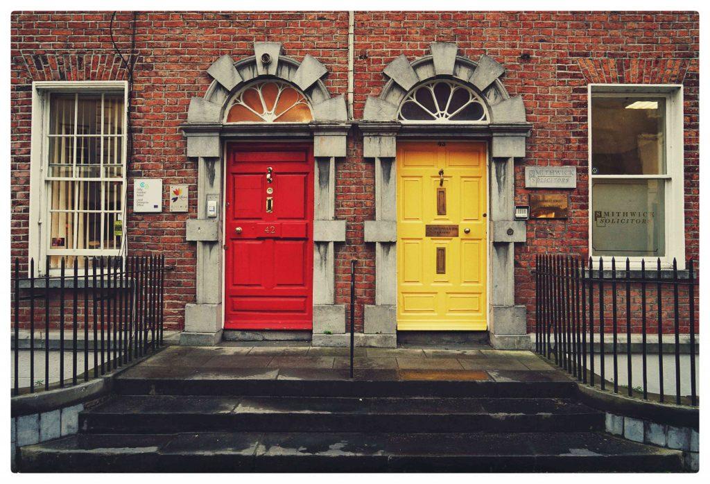 Punainen talon tiiliseinä. Talossa on kaksi ovea, joista toinen on punainen ja toinen keltainen.