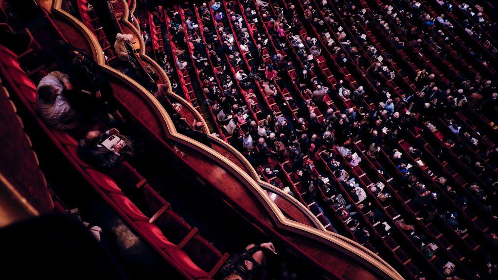 Yleisöä konsertti- tai teatterisalissa, jossa on punaiset penkit.