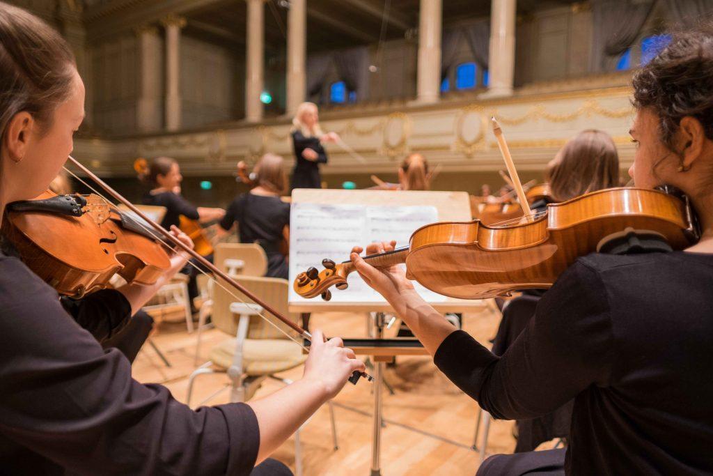 Viulunsoittajia orkesterissa.