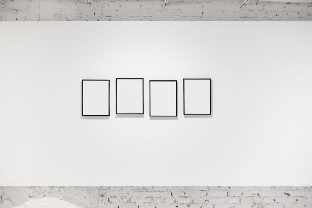 Neljä tyhjää mustakehyksistä taulua näyttelytilassa. Taulut on asetettu hieman eri korkeuksille.