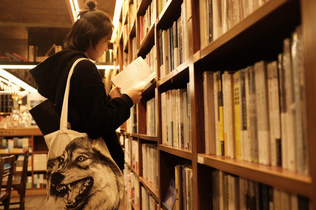 Henkilö selaamassa kirjaa hyllyn vieressä kirjastossa.