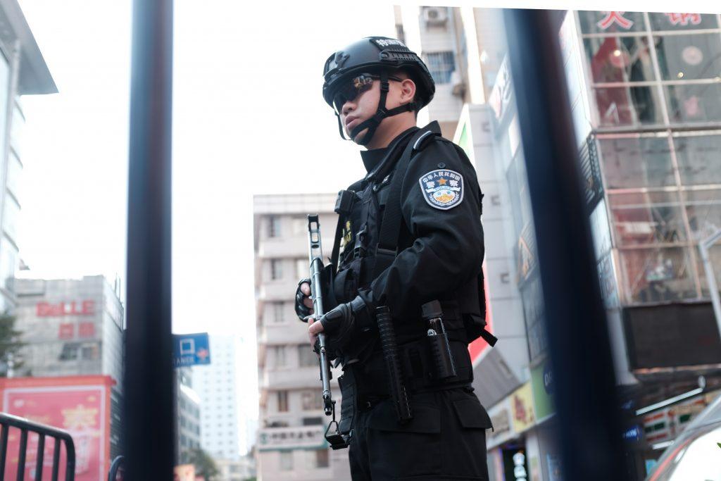 Kiinalainen poliisi, jolla on musta haalari, kypärä ja ase.