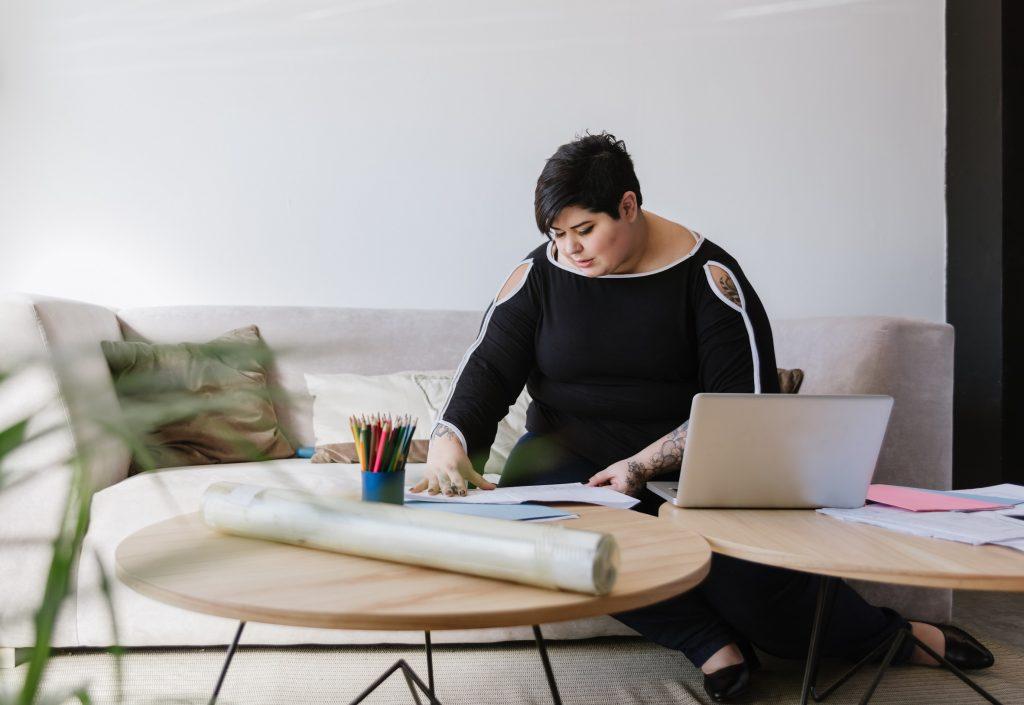 Henkilö istumassa sohvalla. Kahdella sohvapöydällä hänen edessään on papereita, värikyniä ja läppäri.