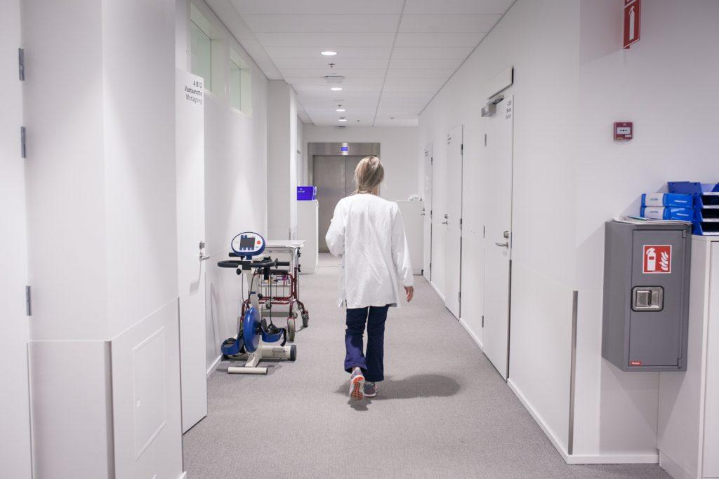 Henkilö kulkemassa sairaalan käytävällä.