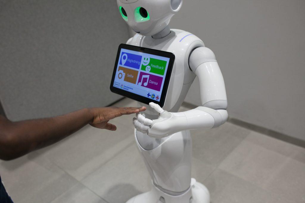 Valkoinen robotti, jonka rinnan päällä on näyttö. Ihminen koskettaa robotin kättä.
