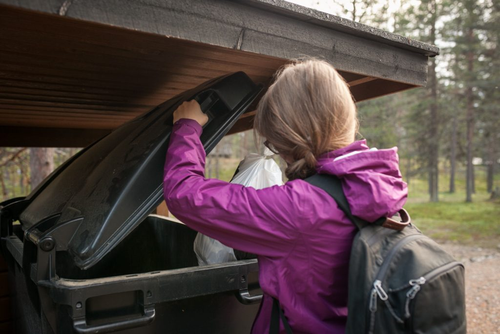 Henkilö laittamassa roskapussia jäteastiaan.