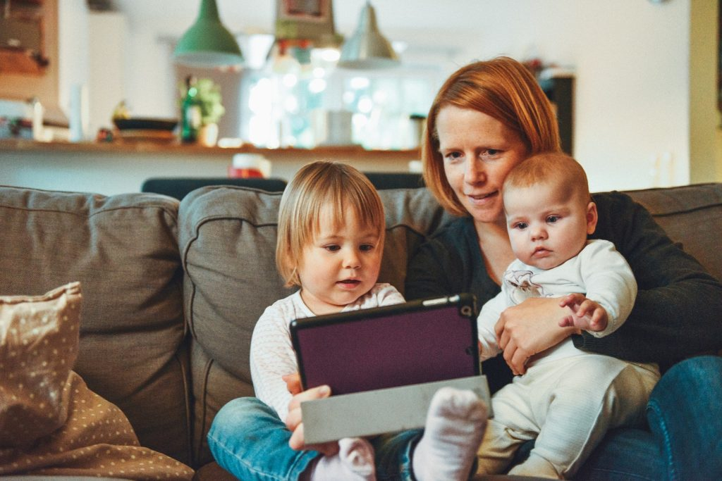 Naishahmo katsomassa tablettia lapsen kanssa sohvalla vauva sylissään.