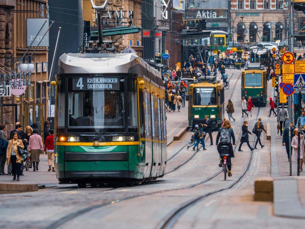 Raitiovaunuja ja vilkas katu Helsingin keskustassa.