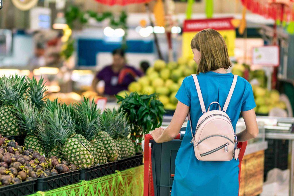 Nainen ostoskärryjen kanssa kaupan hedelmäosastolla.