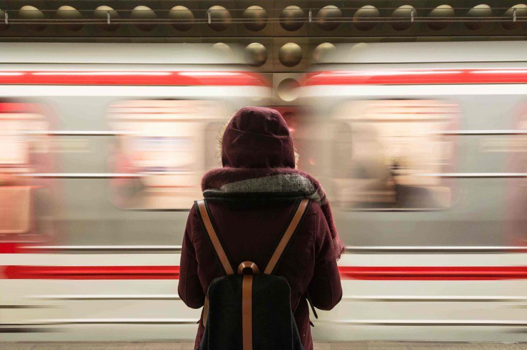 Nuori aikuinen seisoo reppu selässä metrolaiturilla.