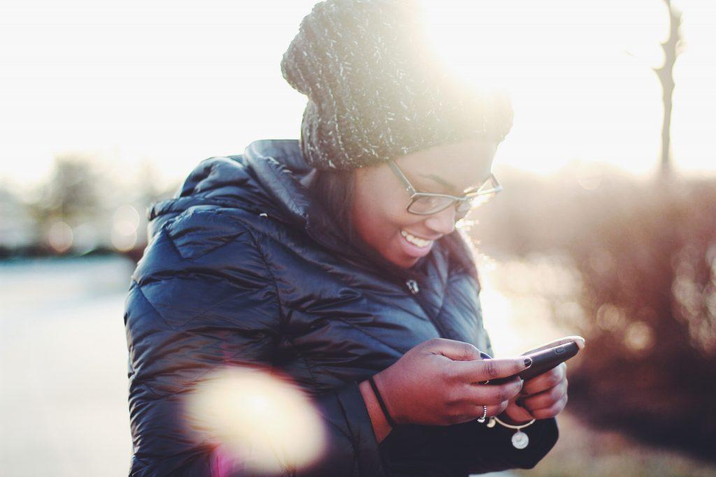 Nainen katsoo älypuhelinta ja hymyilee talviauringossa.