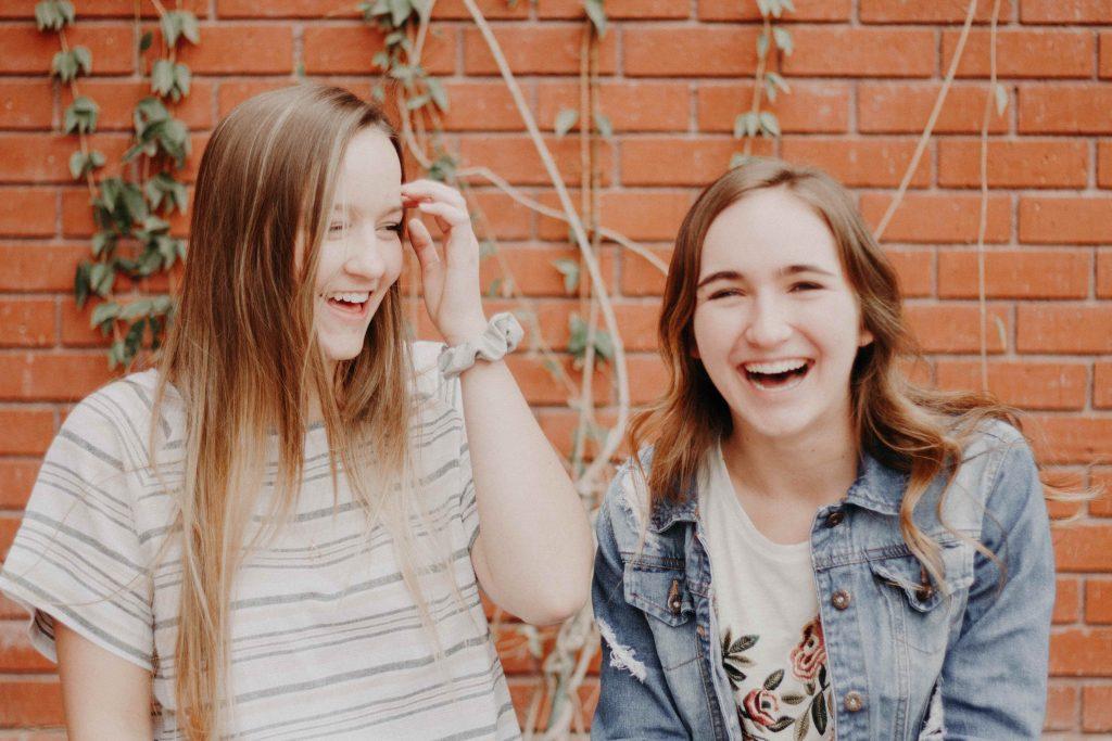 Kaksi nuorta naista seisoo iloisina vierekkäin.