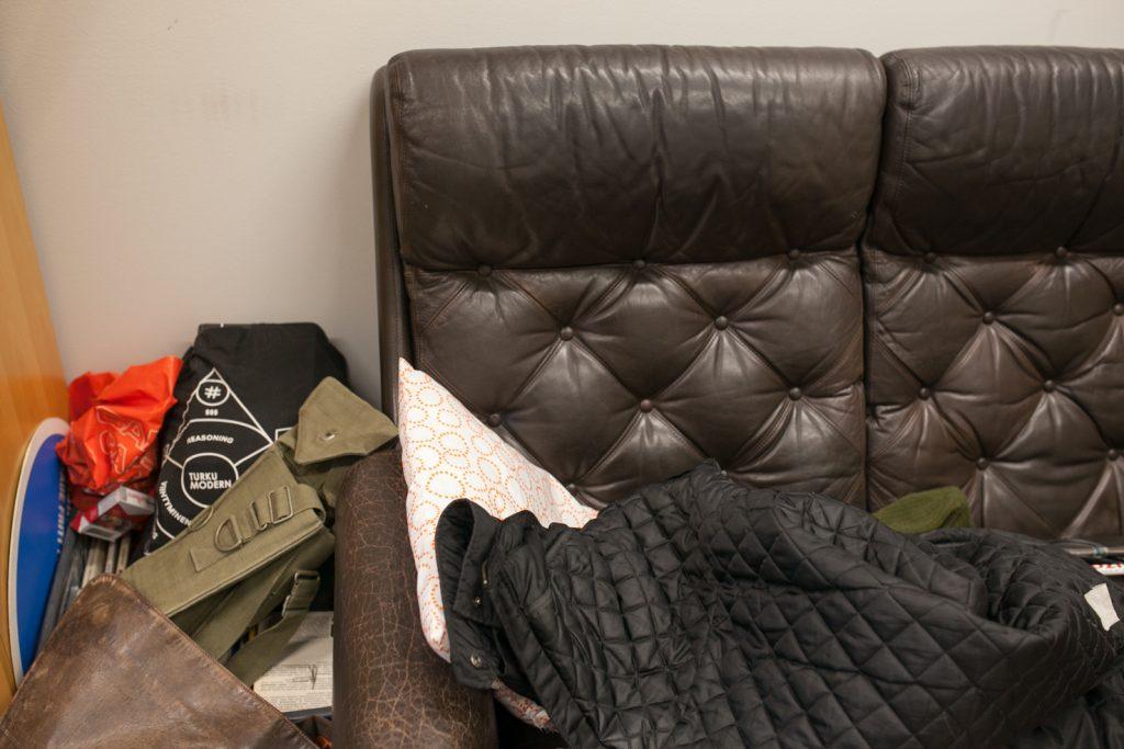 Ruskea nahkasohva, jolla on tyyny ja untuvatakki