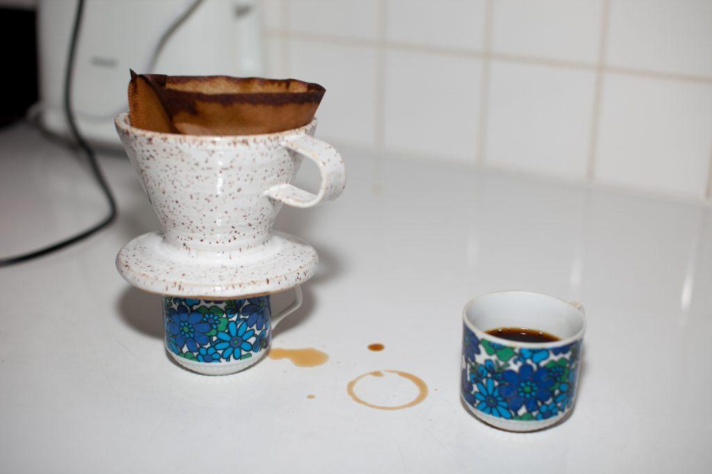 Pöydällä on kaksi kahvikuppia, joista toisen päällä on suodatintötterö.