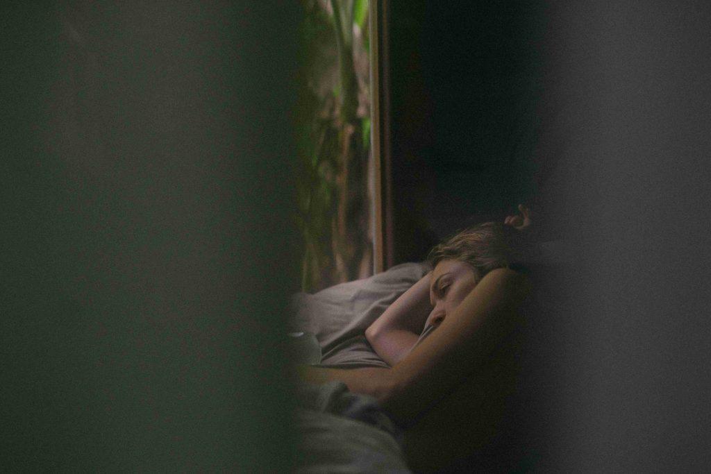 Nainen lepää pimeässä huoneessa.