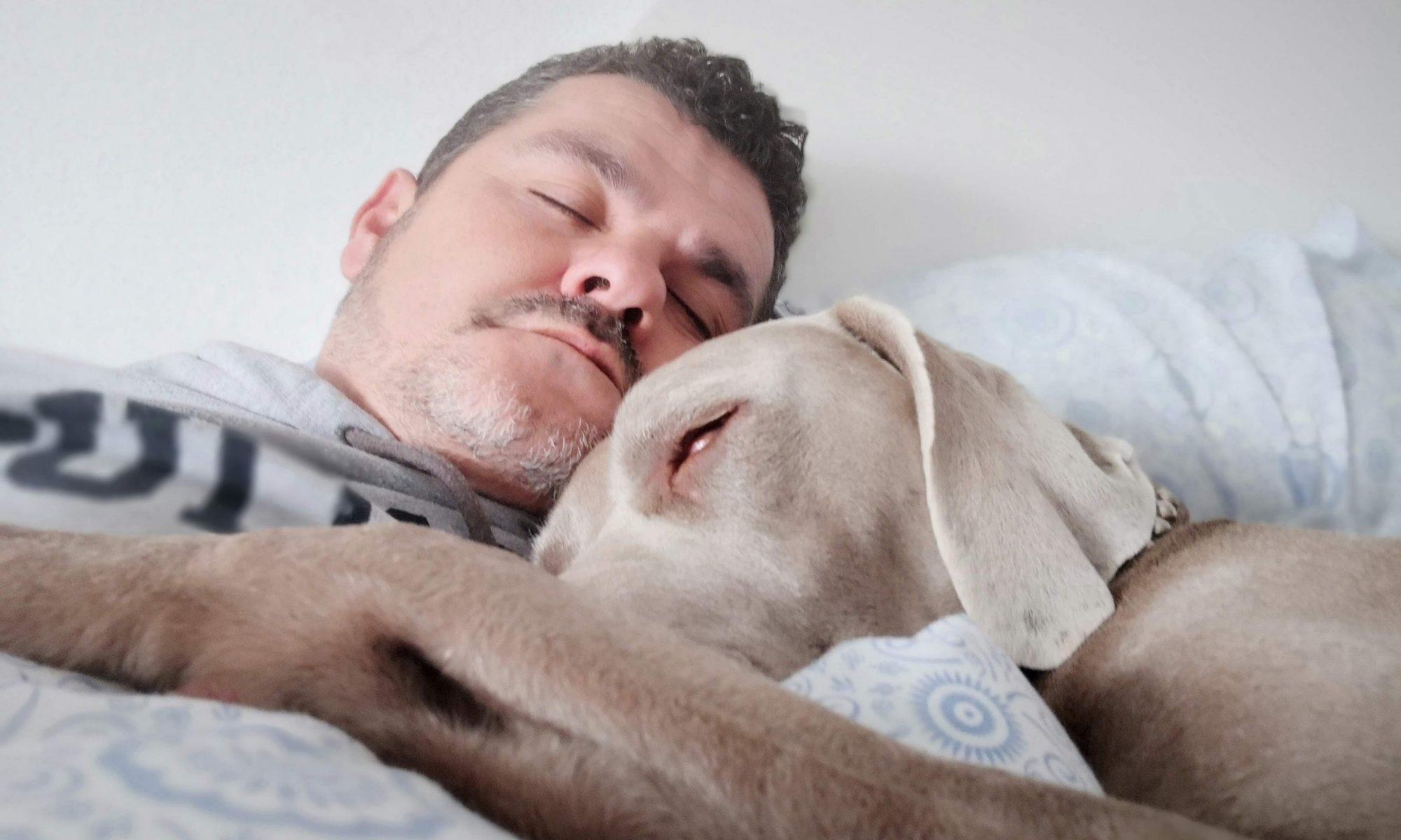 Mies nukkuu vaalea koira kainalossaan.