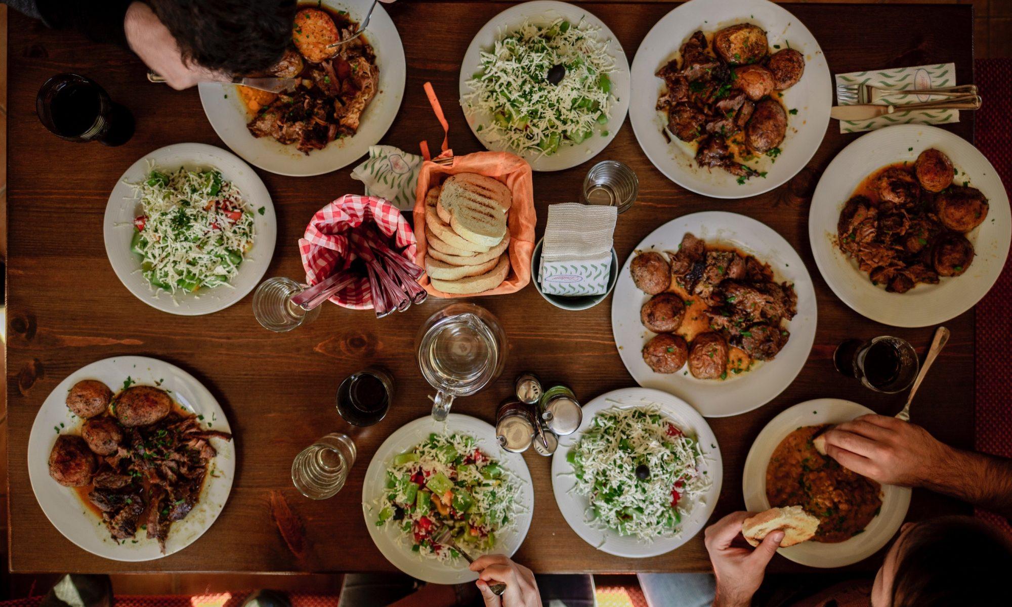 Joukko ihmisiä aterialla, pöydässä monia ruokalajeja.
