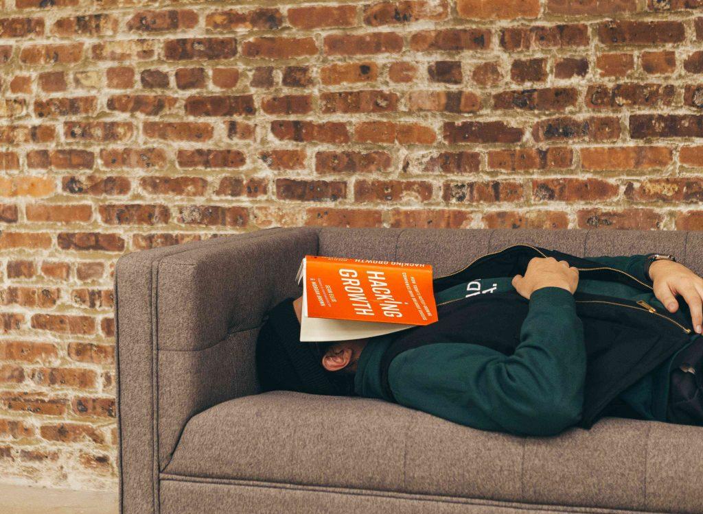 Ihminen nukkuu sohvalla kasvojensa päällä Hacking Growth -niminen kirja