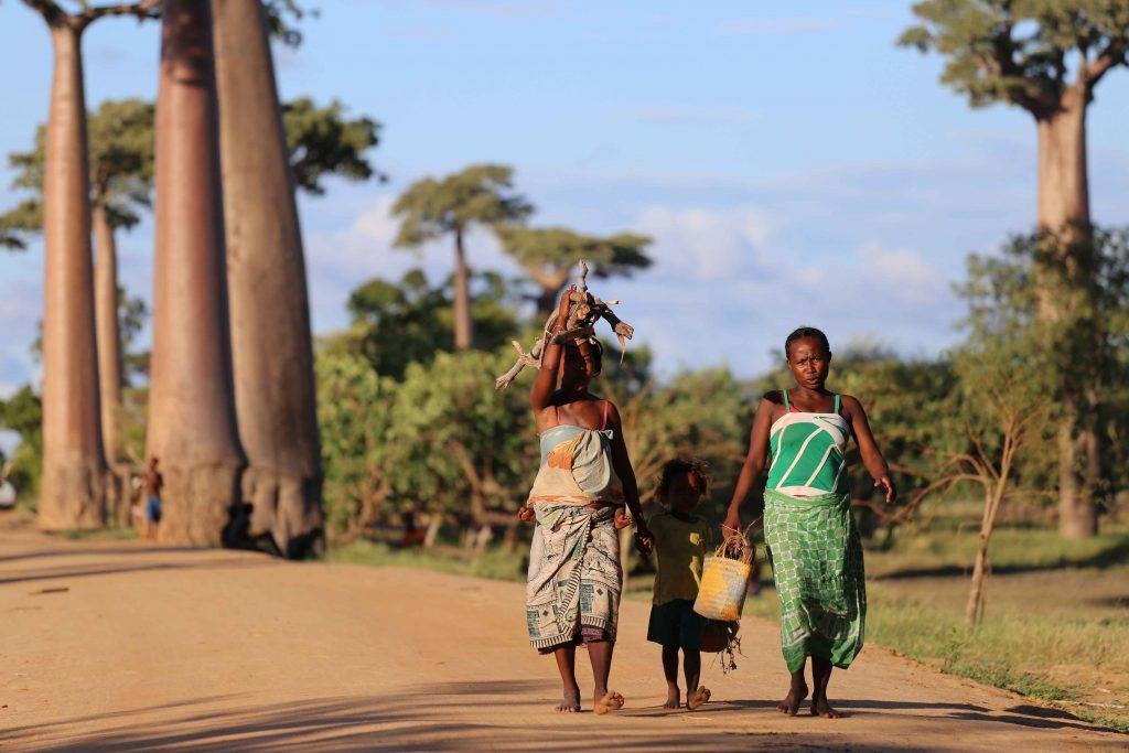 Kaksi naista ja pieni lapsi liikkeellä kantamusten kanssa Madagaskarilla