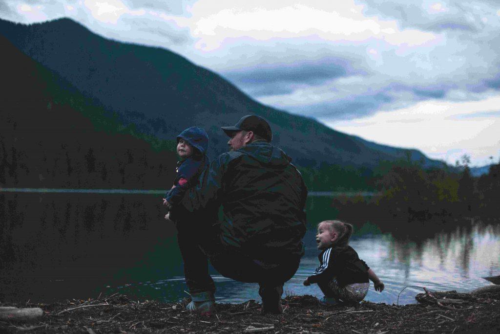 Mies ja kaksi lasta järven rannalla