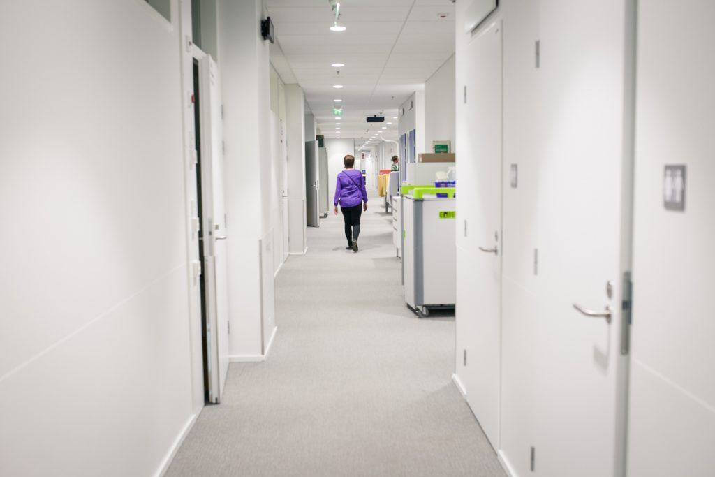 Sairaalan käytävä, jolla kävelee ihminen