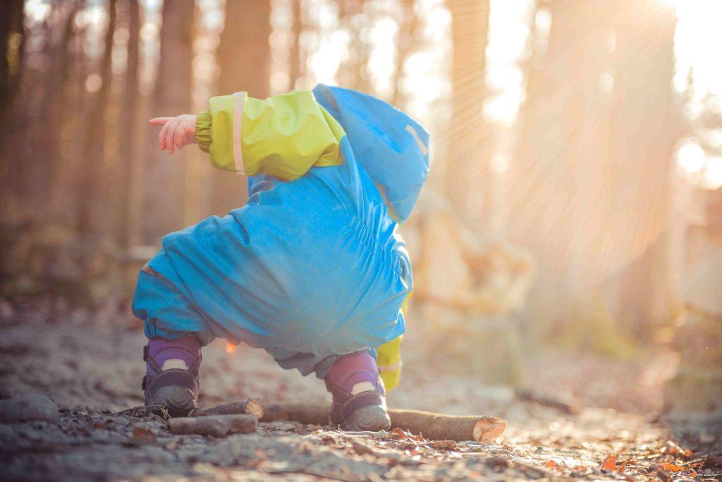 Lapsi leikkii metsässä