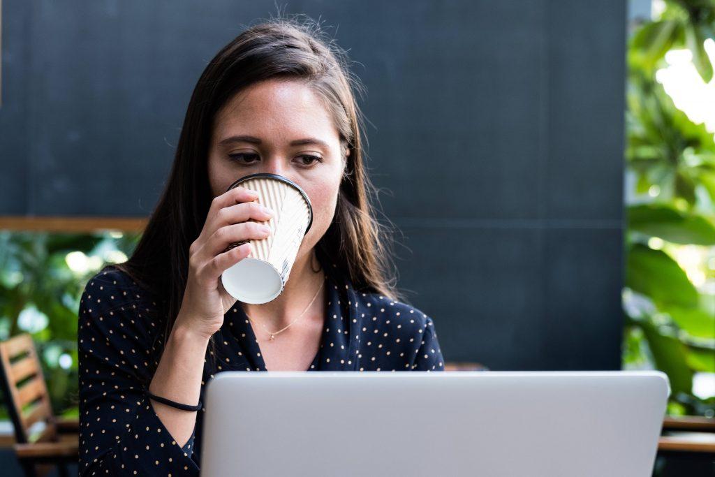 Nainen juo kahvia ja tuijottaa läppäriä