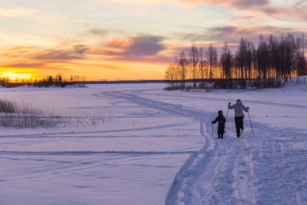 Aikuinen ja lapsi hiihtävät jäällä