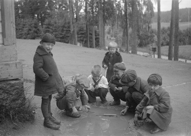 """Inkeriläislapset uittavat lammikossa """"laivaa"""" Oitin väestönsiirtoleirillä 1943. Mustavalkoinen valokuva."""