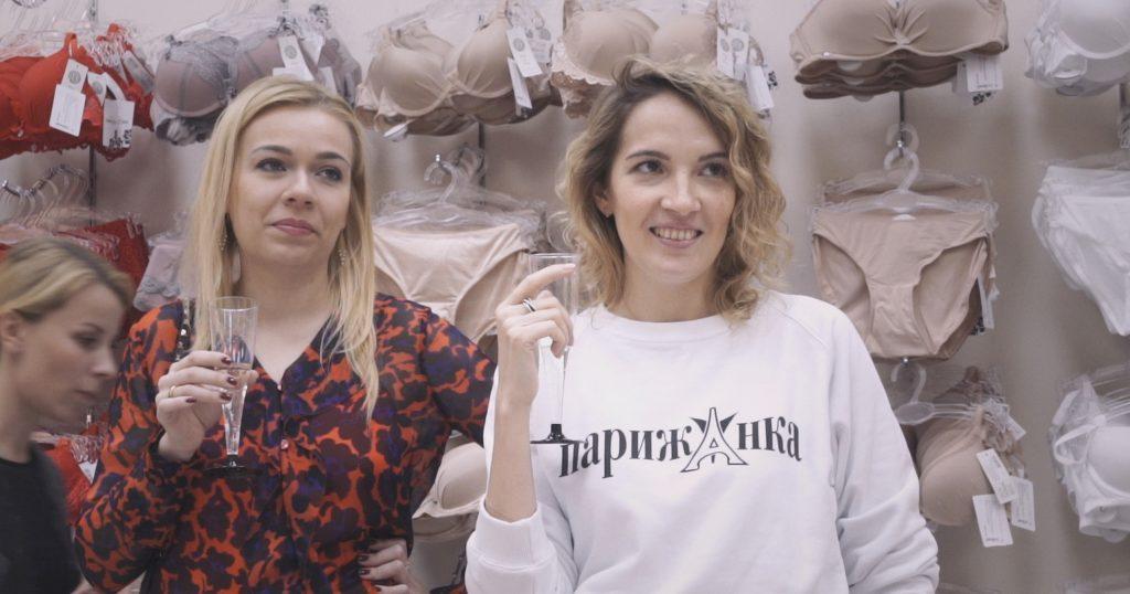 Kolme naista kuohuviinlasit kädessä alusvaateosastolla