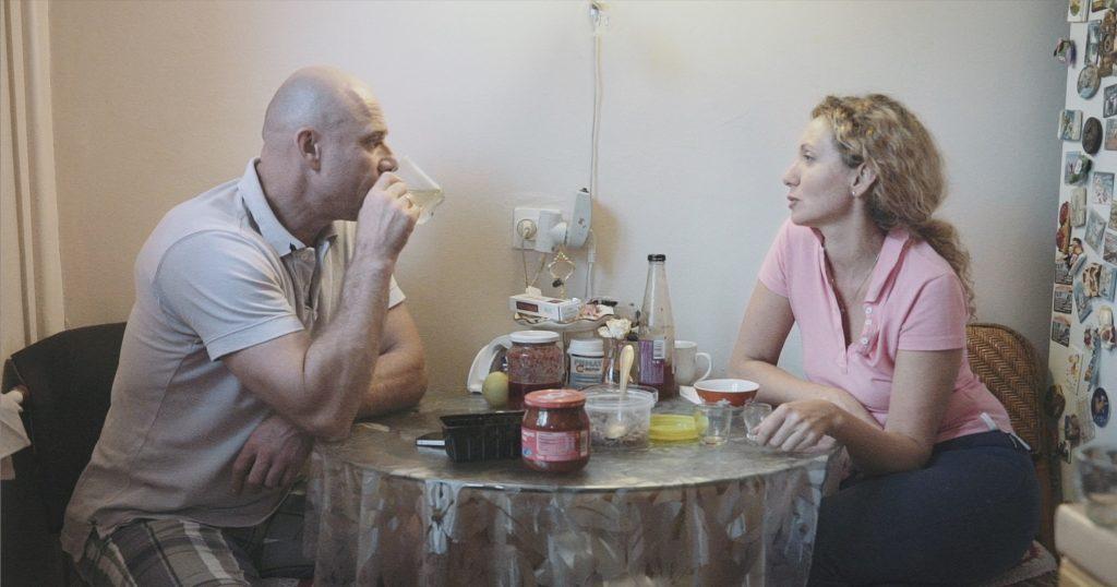 Mies ja nainen keittiön pöydän ääressä