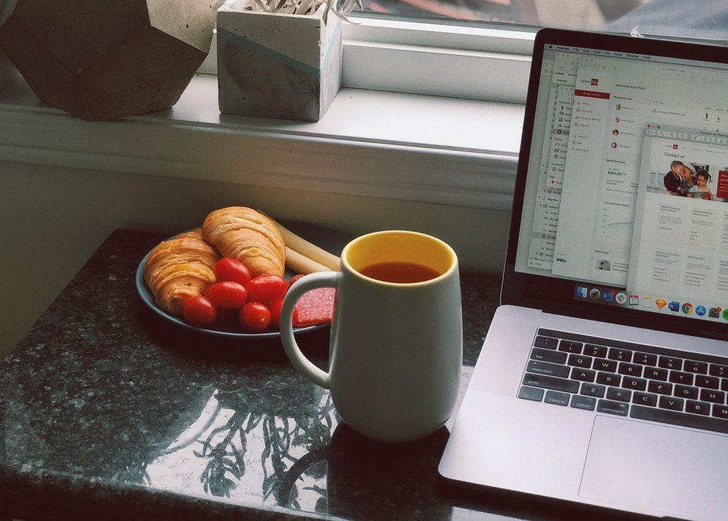 Läppärin vieressä pöydällä kahvikuppi ja lautanen, jolla on kaksi croissanttia ja kirsikkatomaatteja.