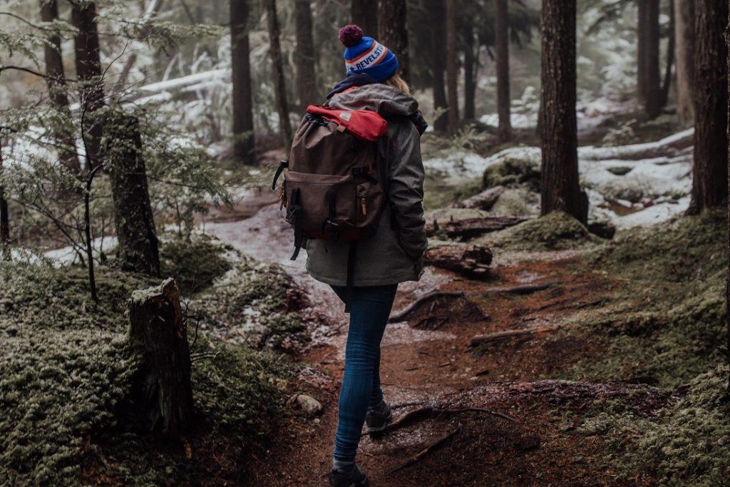 Henkilö kulkemassa kuuraisessa metsässä reppu selässään.