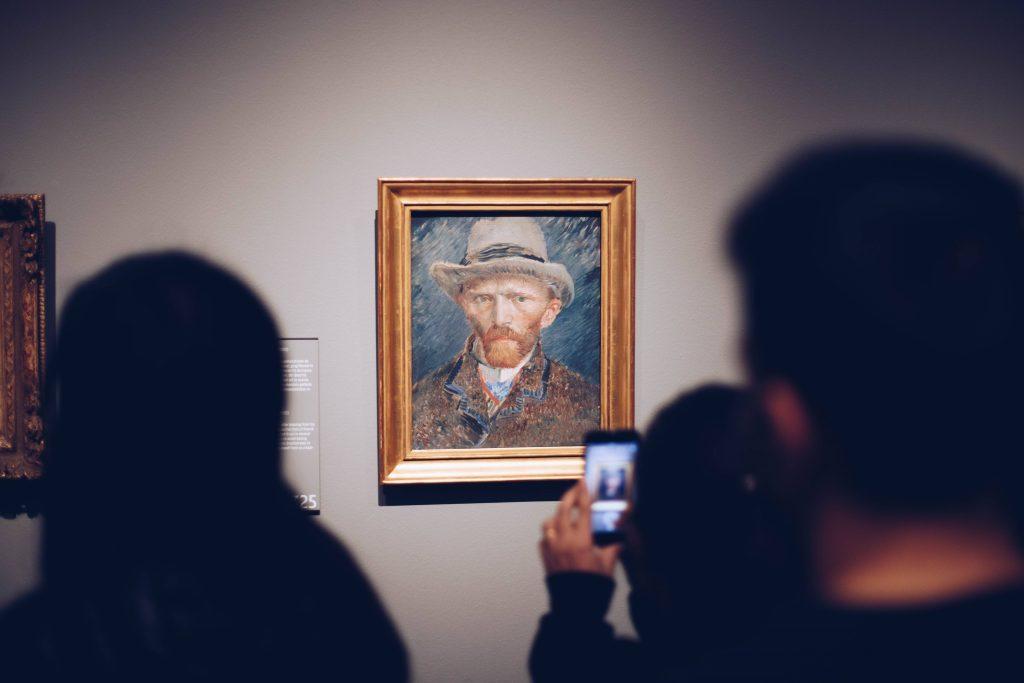 Ihmisiä katsomassa seinälle ripustettua maalari Vincent van Goghin omakuvaa.