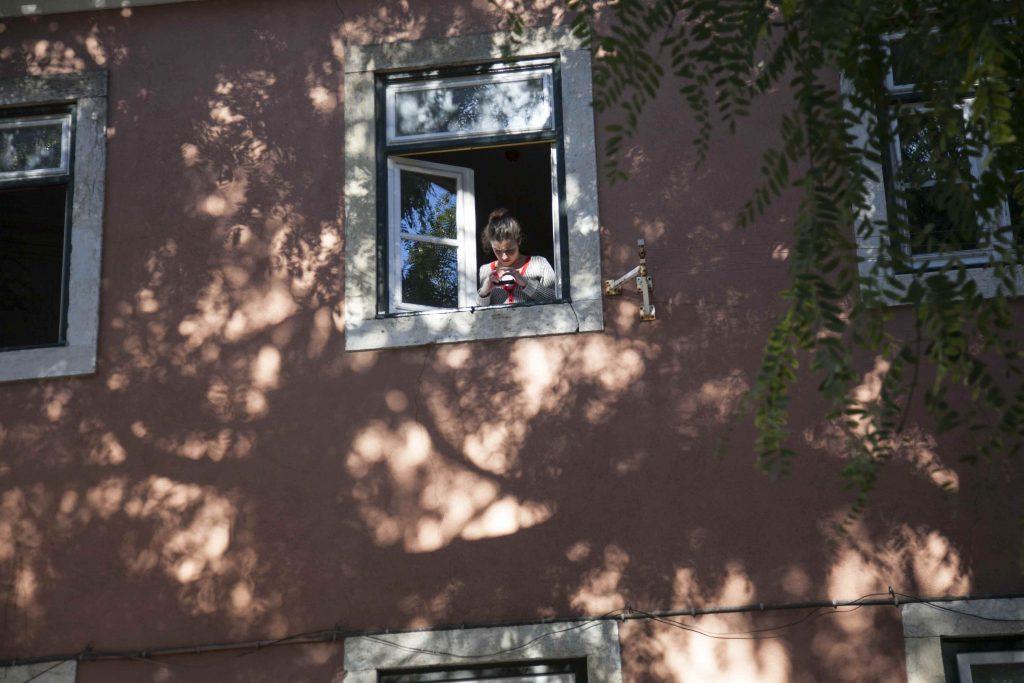Pitkätukkainen ihminen kivisen kerrostalon aukinaisen ikkunan ääressä