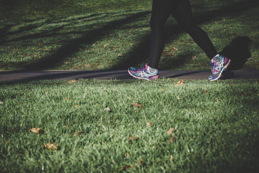 Nurmikkoa ja kävelytie, jota pitkin joku etenee lenkkitossut jalassa