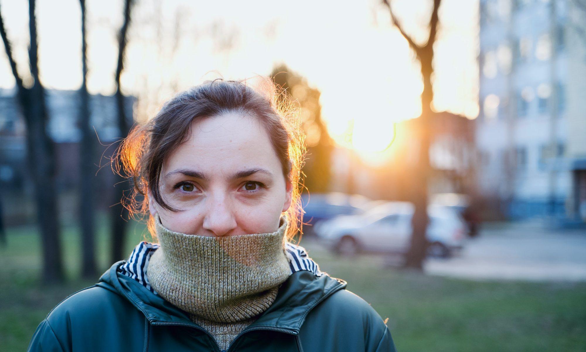 Henkilö katsoo kameraan aurinkoisessa puistossa, poolokaulus suun eteen vedettynä