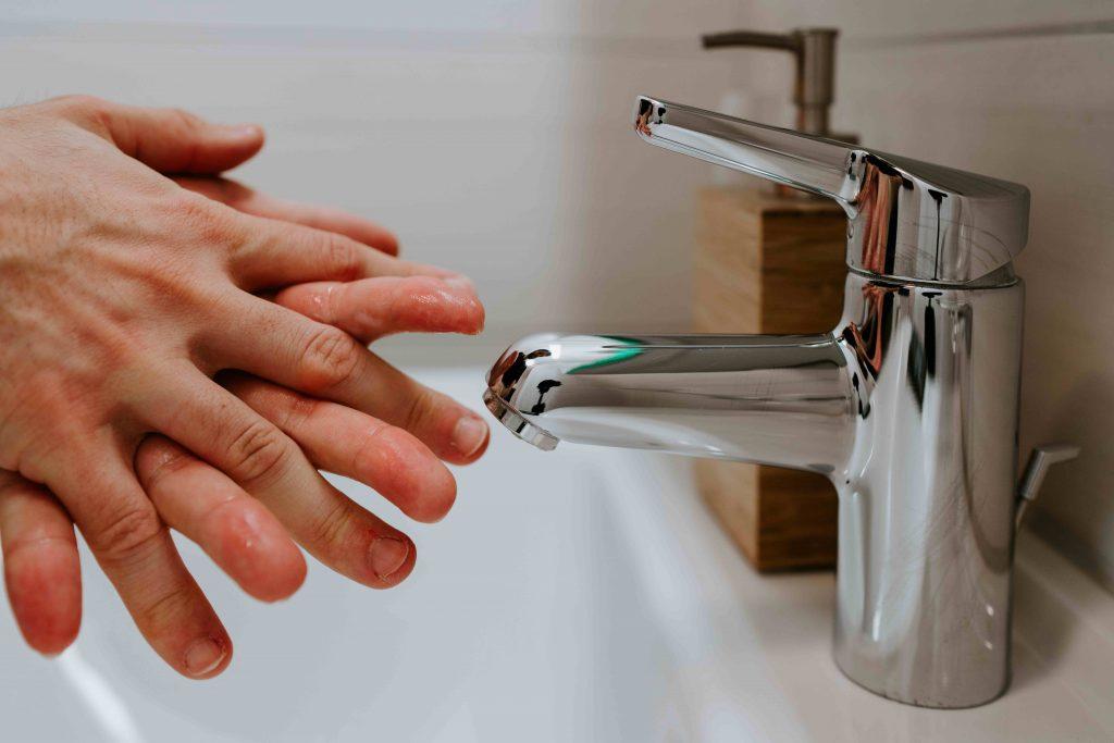 Henkilö saippuoi käsiään vesihanan alla